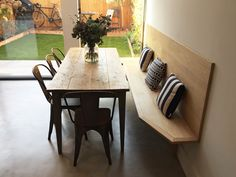 Recycled oak dining table with  a bespoke made oak bench floating across the window