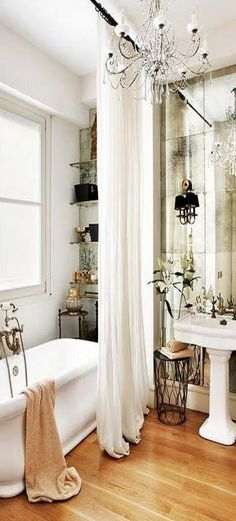 "Bathroom: ceiling high ""bath curtain"", flowers by the sink, small space shelving by tub behind curtain"