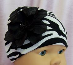 """http://uniquegiftsforher.net/?qpn-pinnable-post=zebra-print-soft-baby-hat-newborn Soft and stretch zebra print hat for babies. This hat features a 4"""" black silk flower with a beaded center. Recommended Ages:Newborn"""