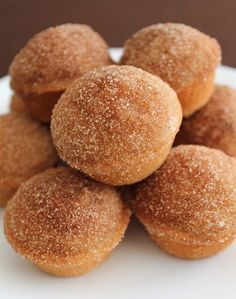 Ten Old Fashioned Cake Doughnut Mini Muffins on a white plate piled on top of each other.