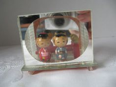 """A pair of intricately painted wooden Kokeshi dolls encased in plastic and mirrored. 1960s; 2 1/4"""" x 1 2/3"""" x 1"""" approximately. $25.00"""