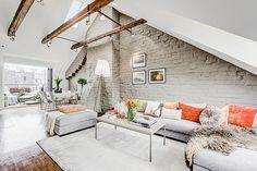 Loft de estilo nórdico que toma prestadas las vigas de madera y la pared de ladrillo vista del estilo industrial.