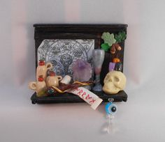 Unique Handmade OAK Witch/Wizard Shelf. An impressive distressed wooden shelf, full of magical needs. Magical manuscript, 3 stone jars, a real Amethyst, a chalice, mojo charm bag, and magicial scrolls, skull candle holder with 3 candles:, one black, one orange, one purple, a rune script spell, a wand tipped with a real peridot gem, a twig of oak & acorns, also an evil-eye protection light catcher hung under the shelf to complete.  Perfect for a Halloween house or witch scene!