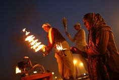 An Indian Hindu priest and a devotee take part during an evening prayer ritual known as Arti at Sangam