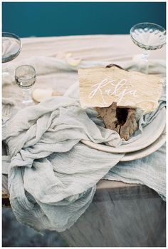 Place setting of white china and beautiful glassware on hand dyed silk with place card of natural paper and white calligraphy. Styling by Janna Brown Design Co., silk by Silk & Willow, calligraphy by Linen & Leaf. Image by Sleepy Fox Photography.