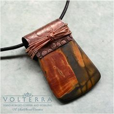 I selected a wonderfully patterned piece of red creek jasper, and decided to use a unique bail. A sheet of copper was hammered, filed, antiqued and formed to fit over the gemstone. Copper wire was wrapped around to hold the pieces together. I suspended this beautiful pendant on 2mm greek leather and finished it off with a hand forged copper clasp. Length is 21 with an additional 1 1/2 for the pendant.    ITEM PN2261