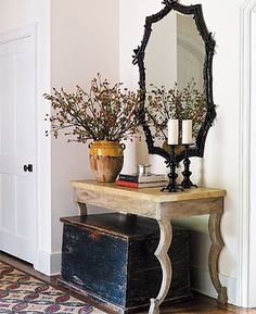 this feels like the entrance to a condo or something. very traditional but with some eclectic pieces that are simply delicious. the rough pine table make a statement with its basic style. i love the vintage box umnderneath.  its has lots of purposes. and the wooden vase, everything, love it all.  walking on sunshine:-)  via:Brabourne Farm
