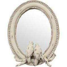 """Add a touch of natural appeal to your living room or foyer with this charming mirror, showcasing 2 birds and beaded trim.    Product: Table mirrorConstruction Material: Resin and mirrored glassColor: Distressed ivory frameFeatures: Includes standBeaded trimTwo bird motifDimensions: 9"""" H x 7"""" W x 1.5"""" D"""