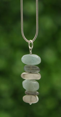Abstract pendant necklace renders a traditional cairn stricture soft and delicate with elements of solid sterling silver and precious gemstones.