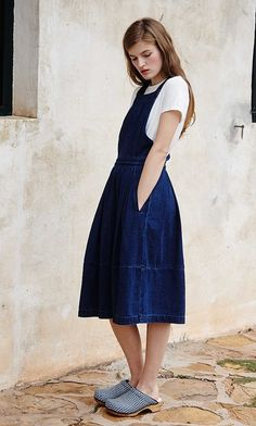 ELVA PINAFORE Indigo denim pinafore dress with simple cross-over strap back. Box-pleat skirt for added volume. Concealed side zip opening. Slanted front slip pockets. Minimal detail. Sidelines. L116cm. Cotton