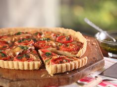 Tomato Tart : Not just for elegant desserts, your tart pan can turn out savory dishes too. Bobby's cheesy tomato-topped tart is built atop a buttery fuss-free crust made with one surprisingly ingredient: extra-virgin olive oil.