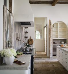 Custom kitchen designed with antique stone flooring and 'La Cornue' luxury stove