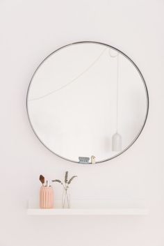 I love a round mirror. Here it is paired with a picture shelf as a vanity unit in this bedroom. The concrete lamp was made by me using a an empty coke bottle as a mould