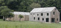 Dřevěný obklad domů je z nehoblovaných modřínových prken s oblinami bez jakékoliv povrchové úpravy