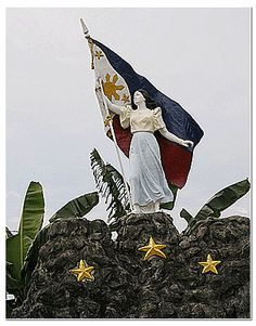 """The battle site is within the compound of Alapan Elementary School in Imus. Highlighted by a 90-foot tall flag pole, the marker features the statue of a woman called """"Inang Bayan"""" standing on three large rocks and holding up the Philippine Flag proudly waving. The monument commemorates the event when the Philippine Flag was first unfurled by Filipino revolutionaries after the victorious battle in Alapan."""