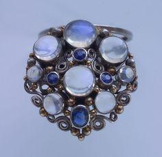 Dorrie Nossiter (1893-1977). Clip brooch. C.1930. Silver, moonstone, sapphire. s.l.