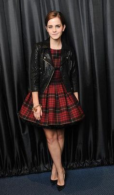 Emma Watson went for a sharp and chic look by rocking her motorcycle jacket with a tartan style dress
