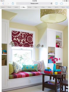 Lilly's window seat.  Love the bright colors on white builtins!