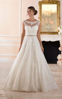 This traditional ball gown wedding dress from Stella York features lace over tulle in a soft A-line silhouette. Layers of tulle are adorned with lace.