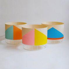 La lampe DOWOOD dessinée par Isabelle Gilles et Yann Poncelet est à la fois brute et sophistiquée.  Elle est consituée d'une base en métal laqué et d'un abat-jour en plaquage de sycomore aux formes géométriques colorées..  Les aplats de couleur mais surtout le sycomore, changent d'aspect une fois la lampe allumée.