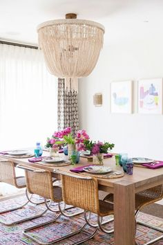 Modern boho with a glam chandelier.  Love how bright and cheery this dining room is.