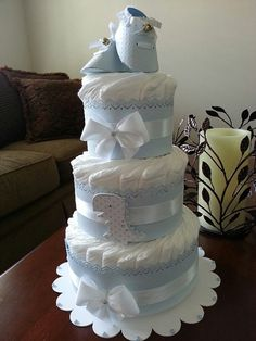 This listing is for one three tier light blue an white diaper cake. The cake stands 15 inches high (with baby shoes) and will arrive to you on