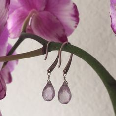 Genuine Amethyst Drop Earrings Purchased from a jewelry boutique on Michigan Ave in Chicago, these genuine amethyst stones have been cut to have hundreds of facets, so the slightest movement catches the light beautifully! Sterling silver French hooks; comes with brand new rubber backs. Jewelry Earrings