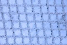patterns of natural frost and snowflakes on a metal grid