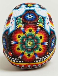 Each of the heavily beaded pieces has been decorated by various artists from the Huichol, using traditional symbols and designs arranged within the patterns, making every skull a completely unique piece of art. The Huichols are decendants of the Aztecs and believe in the Sun God, ancestral spirits and four principal deities – Deer, Corn, Coyote and Eagle. The Sierra Madre Mountains are their home and the Huichol have a long history of creating beaded art, which is big part of their culture.