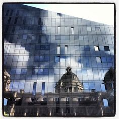 Reflection of port of Liverpool building through new office and apartment block at waterfront.