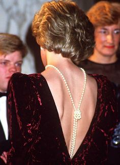 Princess Diana of Wales wearing a long strand of pearls, knotted and flowing down the open back of her crushed velvet evening gown. This picture of Princess Diana was taken at the London premiere of Back To The Future in December, Princess Diana Jewelry, Princess Diana Fashion, Princess Diana Pictures, Lady Diana Spencer, Velvet Evening Gown, Catherine Walker, Queen, Princess Of Wales, Royal Fashion