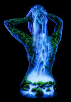 Sandra's Waterfall by John Poppleton This mossy waterfall scene was painted on the models back using fluorescent paint and photographed under black light. Her hair glows under UV and becomes part of the waterfall. #Waterfall #black light #John Poppleton #UV #body painting #figure #fluorescent #moss #nude #rocks #woman