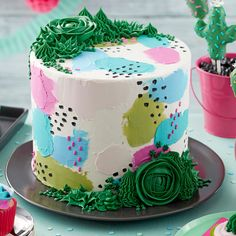Colorful decorations and large succulents abound in this Pretty Pastels and Succulents Cake. Decorated using various shades of blue, green and pink icings, this cake features several decorating techniques for a striking design that will suit any celebration. Add green buttercream succulents along the top and bottom edge of your cake for added style and pizazz!