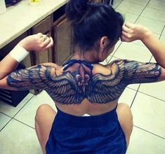cool wing tattoo on upper back for girls