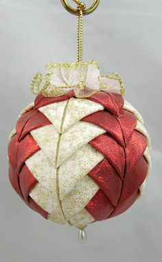 Pinner says - This quilted ornament was created with small pieces of fabric precisely folded to give crisp points. The order of placement determines the final