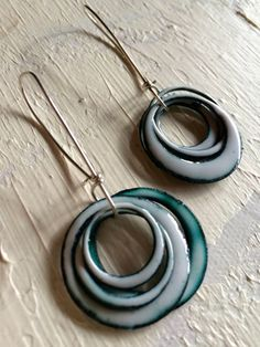 One of a kind white, enamel earrings. They are intentionally over fired to achieve the blue tint color. Handmade Sterling silver ear wires. Made in seattle.