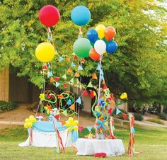 Helium balloons carry streamers or flags staked to the ground around each table.