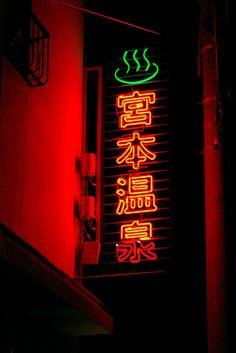 Hot water smokes at red neon Japan