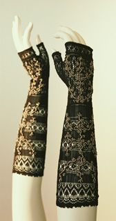 Black silk mitts embroidered with metal beadwork, 1830's. These mitts, reaching to just below the bend of the elbow, have a geometric knit pattern and they are decorated with shiny beads. Because they allow fingers to be freely moved, mitts are more functional than gloves. They became popular in the late 18th century. Some fashion plates of the period depict women embroidering or reading when wearing such mitts.