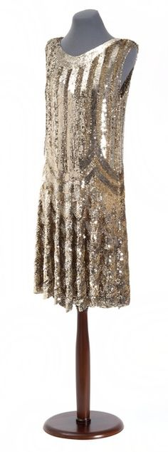 Sequined evening dress, 1928. Sleeveless scoop neck chemise completely covered in bright silver and gold sequins in a stripe and swag design. Made in Paris in the late 1920s.