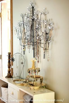 Metal wall art turned jewelry tree I could see this on a much smaller scale for open house events or trunk shows where wall space was plentiful.