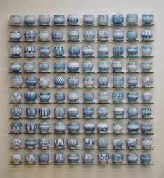 A sculpture made up of many clay pots. Each pot is similar in form but has unique designs.