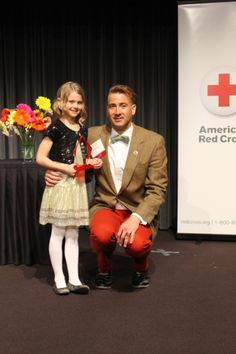 Chris Ihle and his daughter, Elizabeth, 8, pose with Ihle's Red Cross Hero of the Heartland award at an honorary breakfast Friday. Ihle pushed a car caught on a set of railroad tracks out of the way of an oncoming train last summer. Photo by Melissa Erickson/Ames Tribune