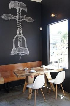 The chalkboard-paint covered wall features a drawing of a French corkscrew. Reclaimed bleacher boards from a local high school gym (complete with graffiti) are used for the bench seating