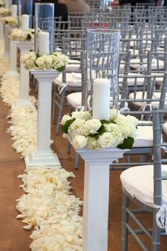 Arrangements of white roses and hydrangeas surround each candleholder.