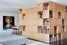 In this modern apartment, the entryway is concealed within the wood bookshelf.