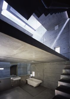"""A bathroom that uses concrete within the design similar to """"House at Big Hill"""" however the smoothness and larger cuts of concrete give the space a different experience, as well as no having any other material to soften the look."""