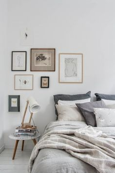 Simple and timeless gray and white bedroom with classic linens, little nightstand, and curated gallery wall.