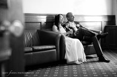 Journalistic style wedding photography of a bride and groom sitting in a room.