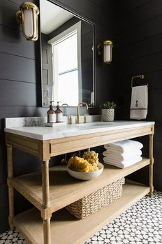 Chic cottage powder room features a black shiplap wall lined with a rectangular mirror illuminates by brass cage wall sconces over a weathered oak and marble vanity, Restoration Hardware Weathered Oak Extra-Wide Single Washstand, atop a black and white cement tile floor, Cement Tile Shop Encaustic Cement Tile Atlas II.